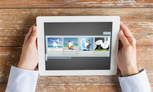 close up of hands with video gallery on tablet pc